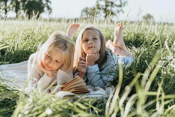 des enfants lisent dans la nature
