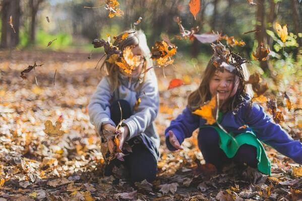 des enfants rigolent avec des feuilles mortes