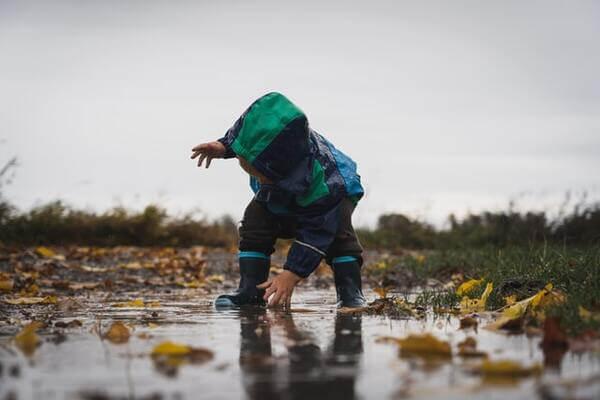 un petit garçon se penche au-dessus d'une flaque